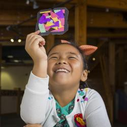"Child holding a tissue paper ""stained glass"" to the light. Credit NISE Network"